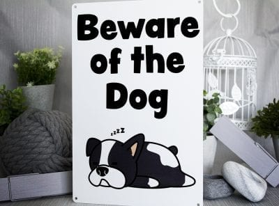 Beware of the dog metal sign with a cartoon sleeping dog on itre of the dog