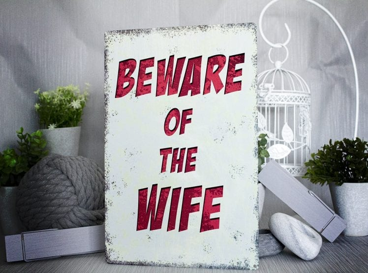 Metal sign with the words beware of the wife on it in red writing