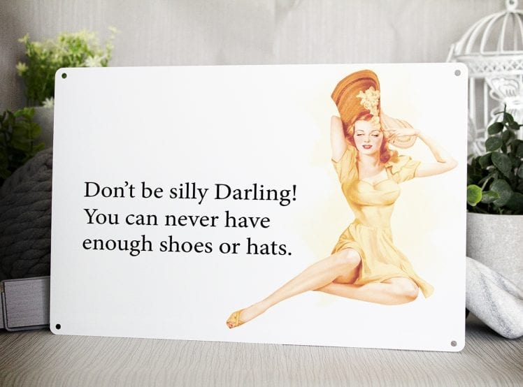 "Metal sign with the words ""Don't be silly darling you can never have enough shoes or hats"""