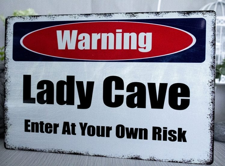 Warning lady cave metal sign