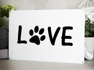 White metal sign with black writing saying LOVE with the O replaced with a dog paw print