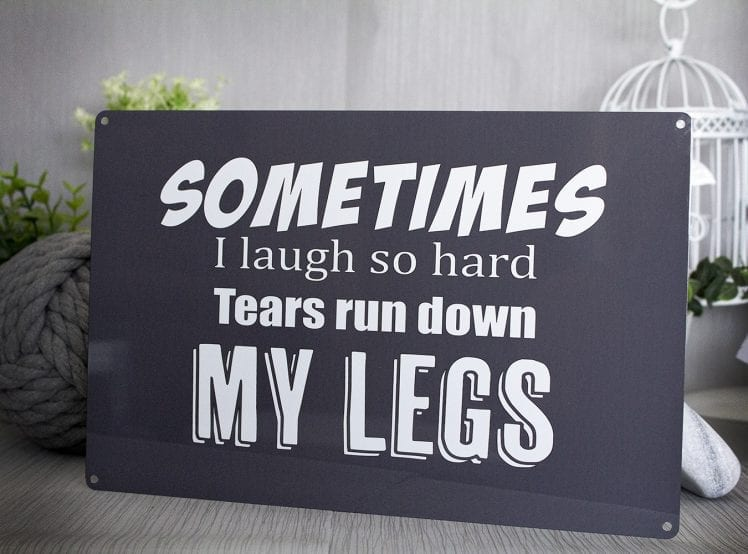 "Grey metal sign with the words ""sometimes i laugh so hard tears run down my legs"""
