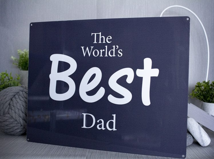 "Metal sign with dark blue background and the words ""The world's best dad"" in white"