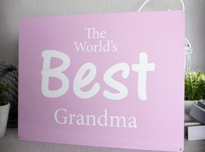 "Pink metal sign with the words ""The best grandma in the world"""