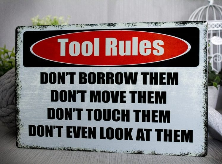 White metal sign that says tool rules on it
