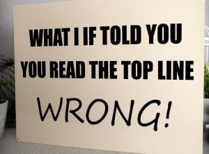"Cream coloured metal sign with black font reading ""What i if told you you read the top line wrong"""