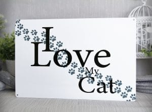White metal sign with paw prints and the words I Love My Cat