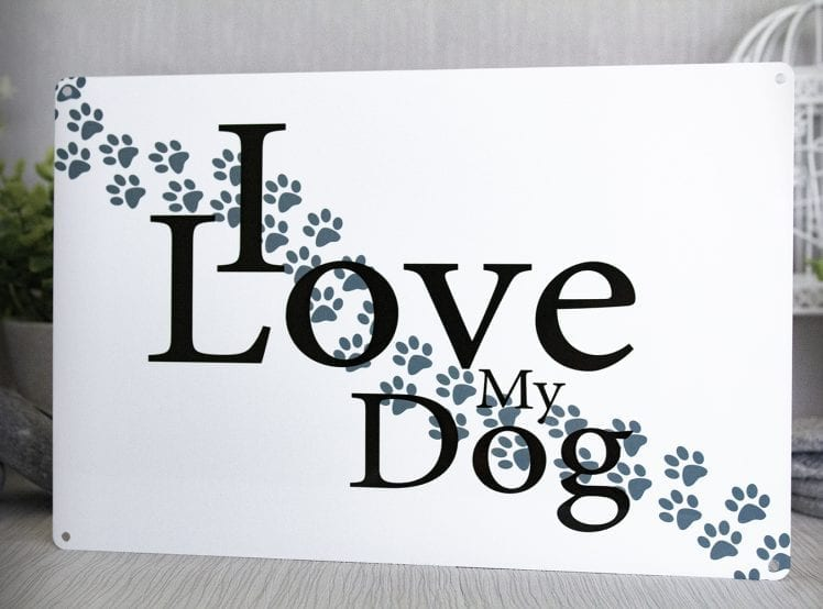 White metal sign with paw prints and the words I Love My Dog