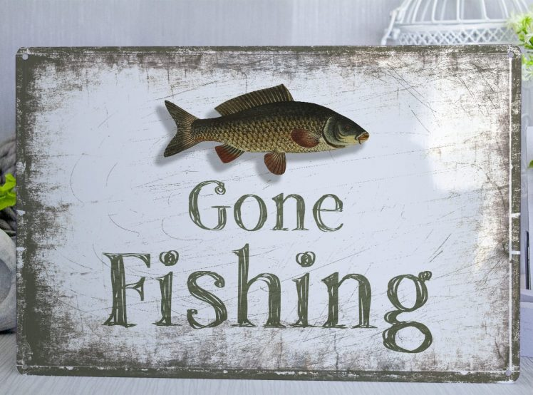 Gone fishing metal sign with a distressed look in green and white