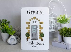 Personalised Family home metals sign with a white background The family name at the top. In the center there is a grey sketched door with 2 potted plants and a stone surround with the words Family Home in black and the year you moved in
