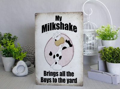 Retro style metal sign with a cartoon cow shaking it's ass and the words My MIlkshake Brings All the Boys to the Yard