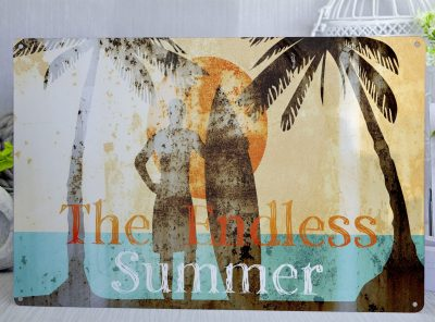 Distressed metal sign with an orange sun in the background and a silhouette of a surfer and 2 palm trees inthe forground with the words The Endless Summer in orange and white text
