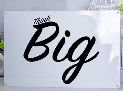 White metal sign with thw words Think Big in black text