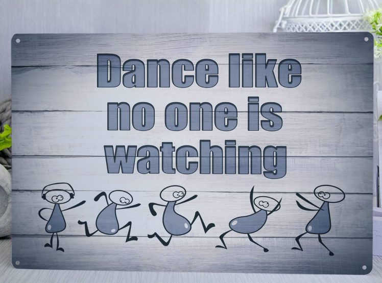 Blue coloured metal sign with the words Dance like no one is watching and stick men at the bottom dancing