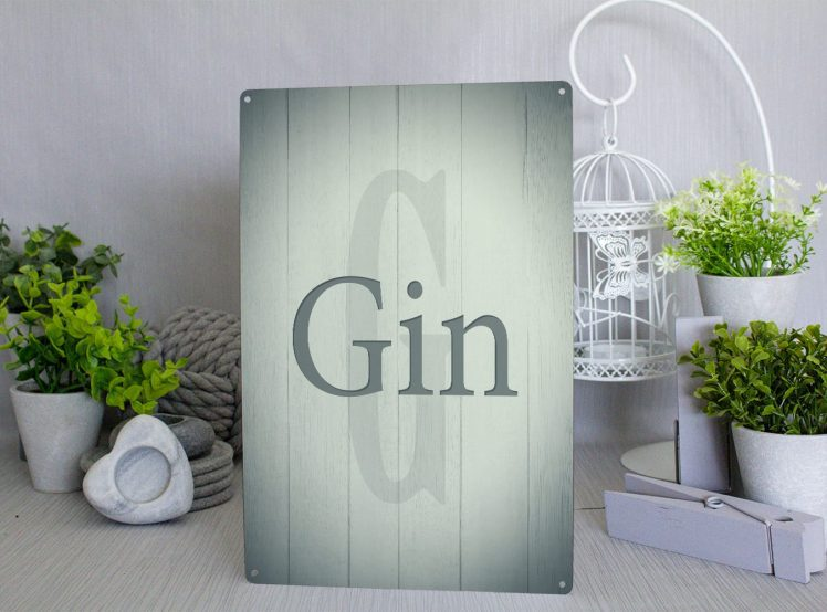 Green metal sign with a large grey G in the background on a wood panel style and the word Gin in green letters in the foreground