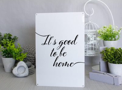 "White metal sign with black text that reads ""It's good to be home"""