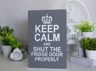 """Grey metal sign with a white Crown and text that reads """"KEEP CALM and shut the fridge door properly"""""""
