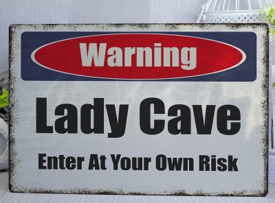 White metal sign with worn edges with a red blue and white warning header and the words lady cave, enter at your own risk