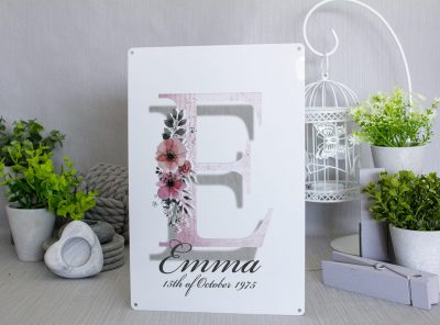 White metal girls name sign which can be personalised with a big pink first letter of the girls name and her name and date of birth in grey smaller writing underneath