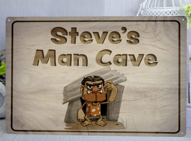 Personalised metal sign with wood effect background and a cave man with the text Your Name Here Man Cave
