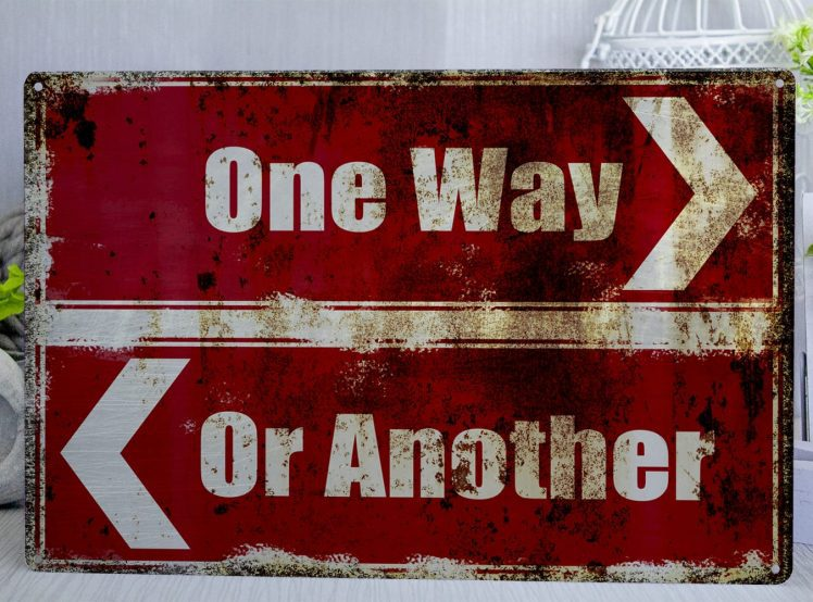 Red and white metal sign in the style of road signs saying one way or another