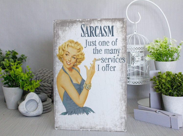 Grey and white distressed metal sign with a blonde pin up woman in a blue dress and blue text that reads SARCASM, just one of the many services I offer