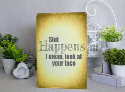 Yellow metal sign with grey text that reads Shit Happens I mean, look at your face
