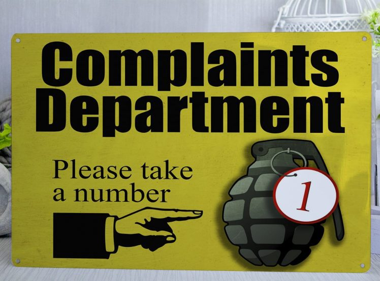 Yellow metal sign with black text that reads Complaints Department please take a number with a nad pointing to a hangrenade with a metal tag that has the number 1 on it