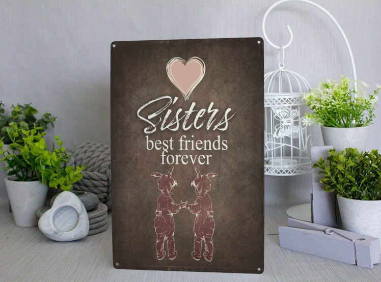 Brown metal sign with a pink heart and 2 small girls in pink rabbit onesies with white text that reads Sisters best friends forever