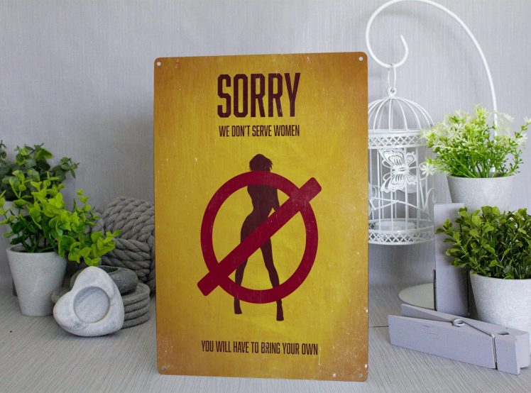 Yellow metal sign with a silouhette of a woman with a red circle and line through her. The text that reads Sorry we don't serve women
