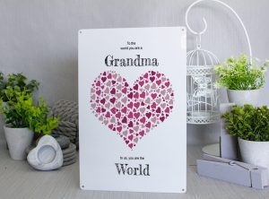 White metal sign With a large heart made of smaller purple and pink hearts and black text that says To the world you are a grandma. To us, you are the world