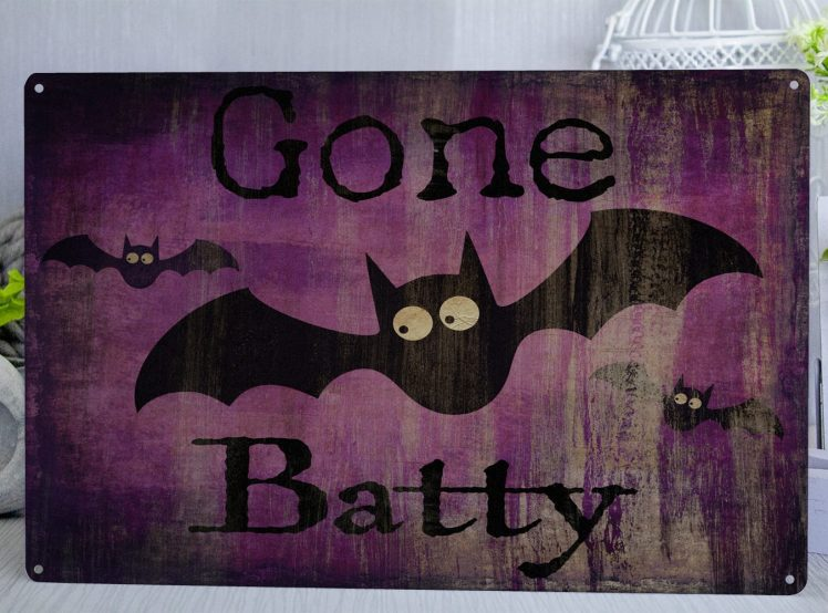Purple metal sign with bats and text saying gone batty